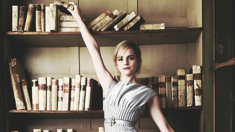 Feature image is of Emma Watson standing in front of a bookshelf, reaching for a book on the top shelf.