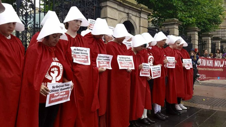 Women in Handmaid's costume protest outside the Dail