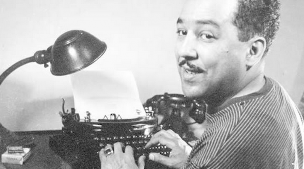 Langston Hughes happily at a typewriter