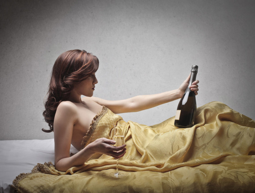 Woman drinking a bottle of wine under the covers