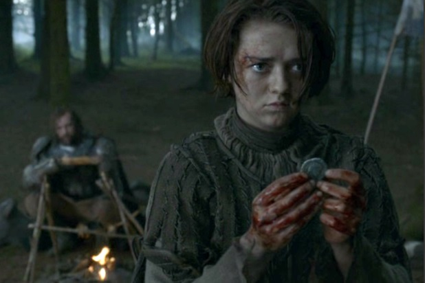 Arya stands with a coin in hand as Sander Clegane lounges in the background around a campfire