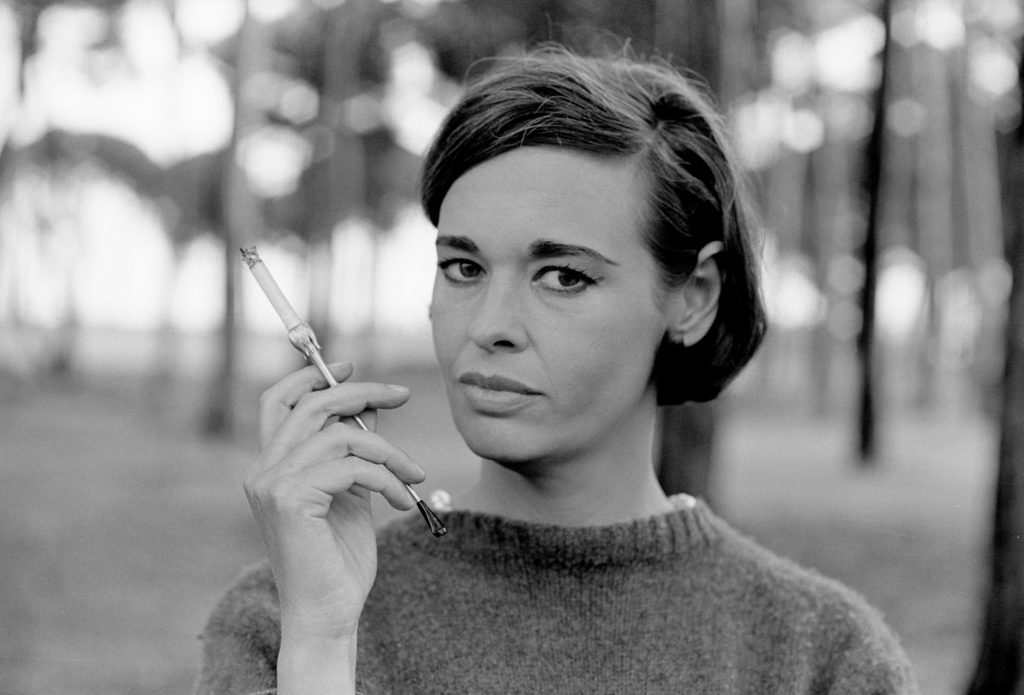 Gloria Vanderbilt holds a cigarette in a black and white photo