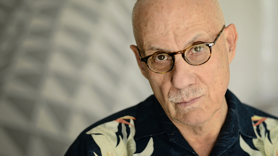 A close up portrait of writer James Ellroy, framed against a white backdrop