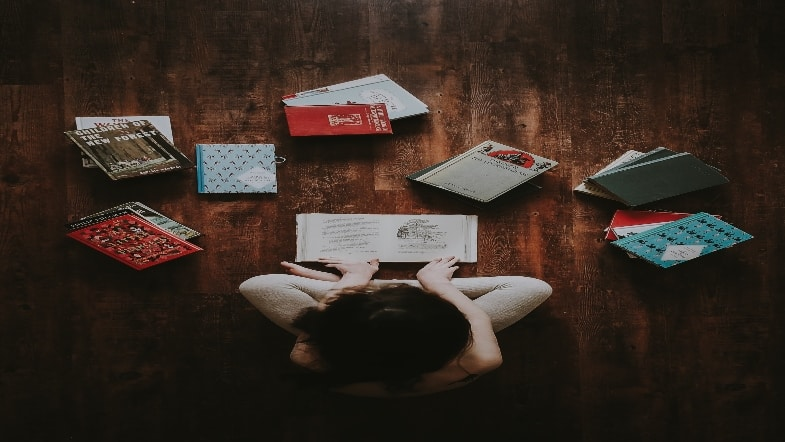 Girl surrounded by books and reading