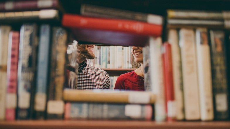 Man and woman's faces hidden by books in library