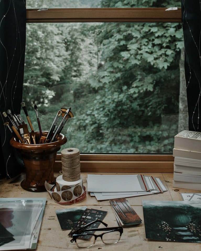 Image of a desk with writing utensils and paper on in with a window in the background that shows a forest