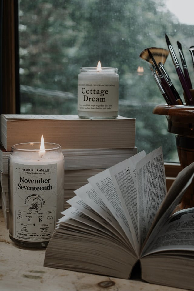 image of a book opened on a table surrounded by candles