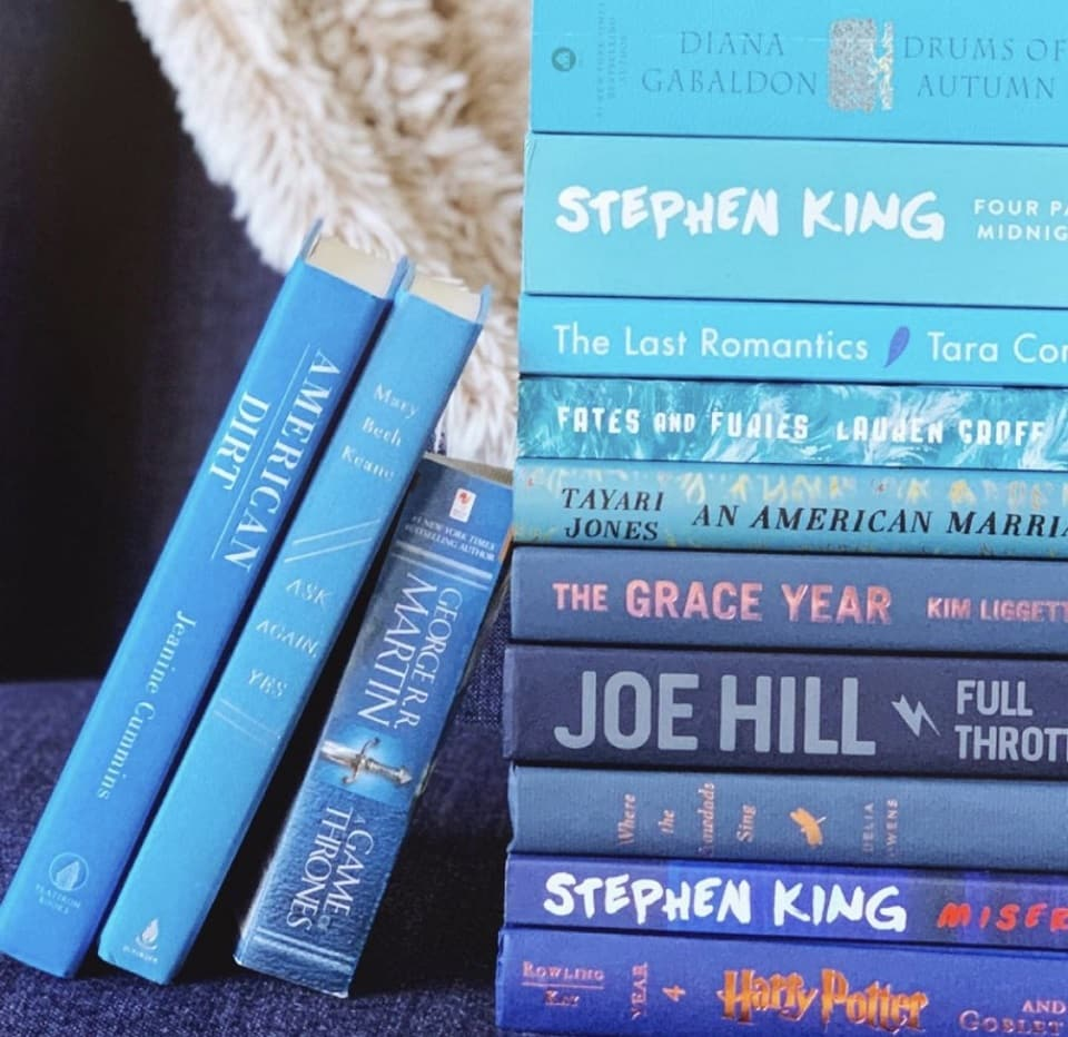 Image of a stack of books with several other books leaning against the stack