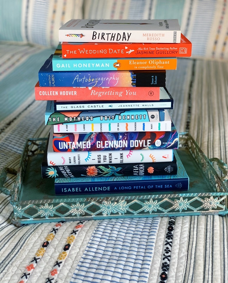 A stack of books sitting on a sofa